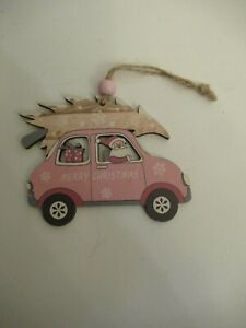 Little pink hanging wooden Santa in car with Christmas tree on roof decoration