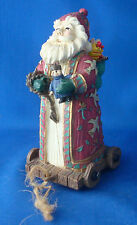 """5¾"""" tall Santa Claus figurine on pull toy base wearing doves on his robe"""
