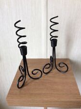 A PAIR OF BLACK METAL CANDLE HOLDERS