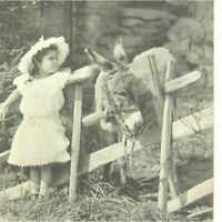 Antique printed postcard portrait of a cute young girl petting a donkey