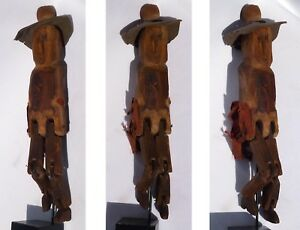 A Jointed carving of a very primitive man wearing a felt hat with tacks for eyes