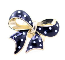 Gold and black enamel bow ring with white spot, UK Size P