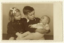 """DO WE HAVE TO KEEP HIM?"" TWO KIDS UNHAPPILY INSPECT THEIR BABY SIBLING (RPPC)"