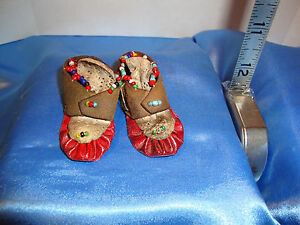 """Small leather moccasins with seed beads and dyed red soles, 2.25"""" long 1"""" wide"""