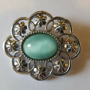 A beautiful silver tone brooch with a pale green stone