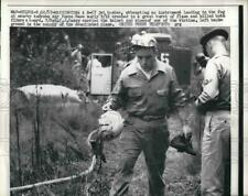 1957 Press Photo T/Sgt PJ Casey carries one of the helmet of the pilot of the
