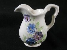 Small porcelain, raised flower pitcher with butterfly mark on bottom