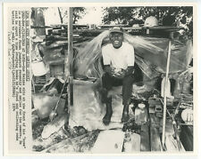 1974 GUS HAINES SMILES/SITS AT FRONT OF HIS MIAMI JUNKYARD HOME BW PHOTO