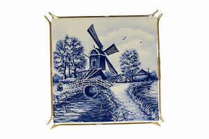 A blue and white windmill tile trivet / teapot stand