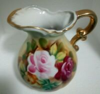 """Vintage ceramic red white and pink white floral pitcher 8"""" H 5' W T-2007 MARK."""