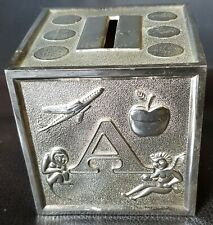 SILVER COLOURED METAL A B C MONEY BOX WITH TWIST OFF STOPPER.
