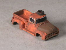HO 1956 Orange Rusted Out Ford Pickup with tire on roof.
