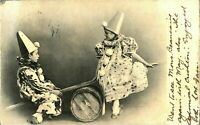 Antique printed postcard cute children dressed as clowns on a barrel seesaw