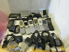 Lot of older mixed Cell phones, chargers, and Garmin electronic devices.