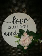 "Round Wall Plaque With The Inscription: ""Love Is All You Need."" Has Flower."