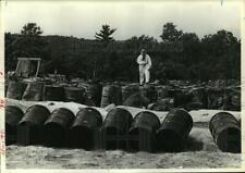 1981 Press Photo Man in protective suit stands on chemical waste barrels
