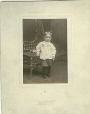 YOUNG CHILD W/ WICKER CHAIR & DOLL