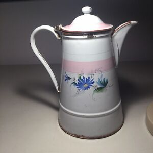 Antique white French enameled coffee pot with flowers around.