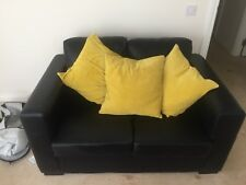 Small, black two seater faux leather sofa in very good condition.