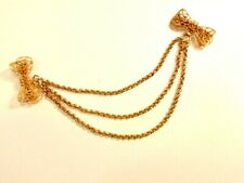 shaped pins joined by 3 chains gold colored sweater pin with 2 bow