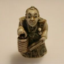 More details for netsuke highly decorated figurine man holding papers and basket