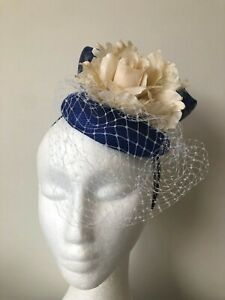 Royal blue fascinator with sinamay loops, cream flower and netting on a headband