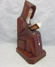 Carved wood figurine of seated monk reading a book