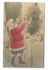 Embossed / Bas Relief CHRISTMAS PC showing Santa with blue pants decorating tree