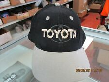 "TOYOTA-BLACK CAP W/ TAN BILL-""TOYOTA"" IN GOLD THREAD ON TOP OF CO. LOGO IN BLACK"