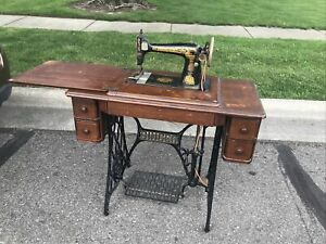 singer treadle sewing machine in cabinet