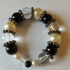 A lovely elasticated bracelet with black, cream and clear beads