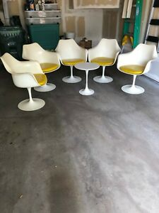 5 knoll saarinen white tulip chairs with yellow cushions and small side table.