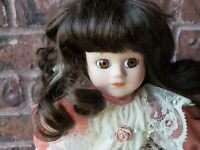 Vintage porcelain doll with metal stand Brunette hair and brown eyes pink dress