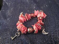 Wonderful elasticated bracelet with shell pieces in pink and silver tone charms