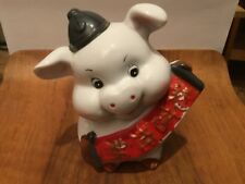An unusual hat wearing, Chinese banner holding large ceramic piggy bank