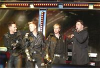 A 12 x 8 inch photo featuring Westlife, personally signed by Shane Filan.