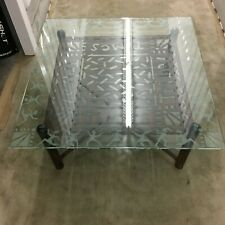 "Wrought iron coffee table with frosted glass top, ""Tribal Times"" across base"