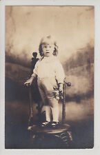 LITTLE BOY WITH FLOWER ON TOP OF CHAIR. STUDIO PHOTO. ANTIQUE REAL PHOTO RPPC