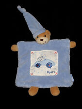 Doudou plat Ours marron écru et bleu Kaloo lapin conduisant une voiture
