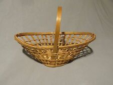 "Small wicker basket with handle open weave oblong shaped. Light bamboo 6"" tall"