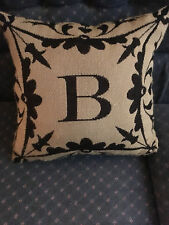 "Oversized couch pillow black with letter ""B"" on tan background"