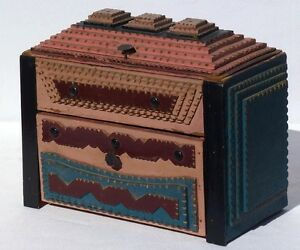 A colorfully painted tramp art box with a drawer and hinged lid.