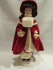 "8 1/2"" PORCELAIN DOLL WITH A RED CAPE AND HAT, WHITE MUFF AND STAND"