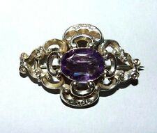 ANTIQUE VICTORIAN YELLOW METAL BROOCH WITH AMETHYST CABOCHON.