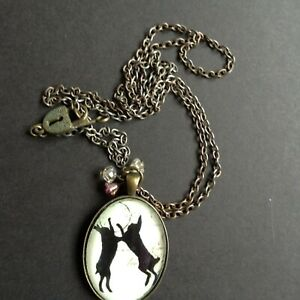 Glass faced picture pendant of two fighting hares with lock and key fastening