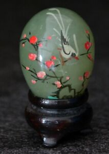 Hand painted jade egg decorated with small bird and flowers, on a wooden stand
