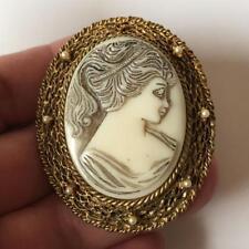 Vintage bone color carved Cameo in gold tone textured finish oval fra. Lot 61I