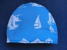 Boats and beach huts on blue Tea Cosy