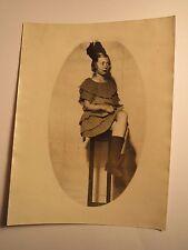 Mädchen im Kleid sitzt mit übergeschlagenen Beinen auf Hocker - Buch / Foto