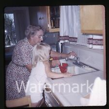 1960s  amateur Kodachrome Photo slide Young girl and lady in kitchen